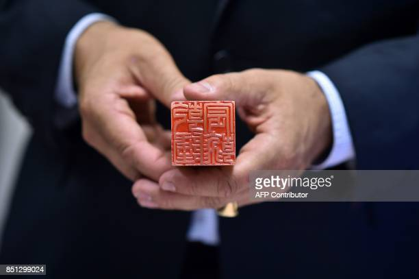 French auctioneer Jérôme de Colonges poses with the personal seal of China'e Emperor Qianlong in Toulouse on September 22 ahead of its scheduled...
