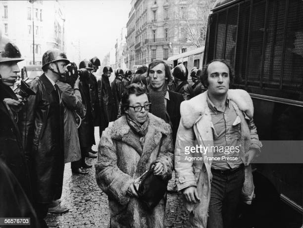 French author and film director Marguerite Duras and other unidentified protestors walk past a line of police officers on their way to a police truck...