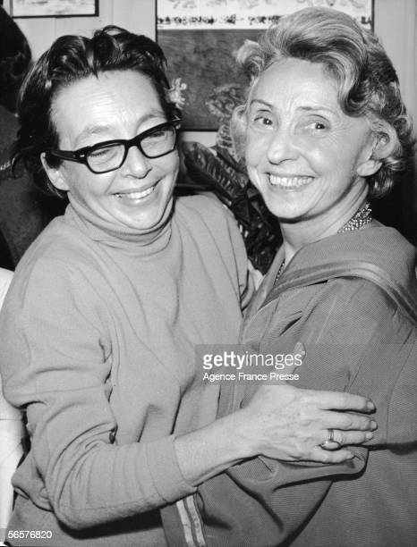 French author and film director Marguerite Duras smiles as she hugs actress Madeleine Renaud Paris December 3 1965