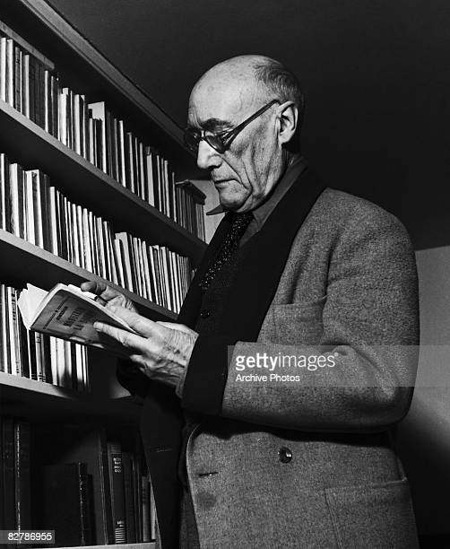 French author Andre Gide selects the novel 'Monsieur le Souris' by Georges Simenon at his Paris apartment, circa 1945.