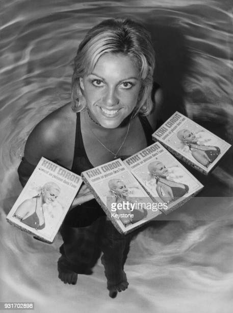 French backstroke swimmer Christine Caron aka Kiki Caron surrounded by floating copies of her autobiography 'Comme un Poisson dans l'Eau' Paris...
