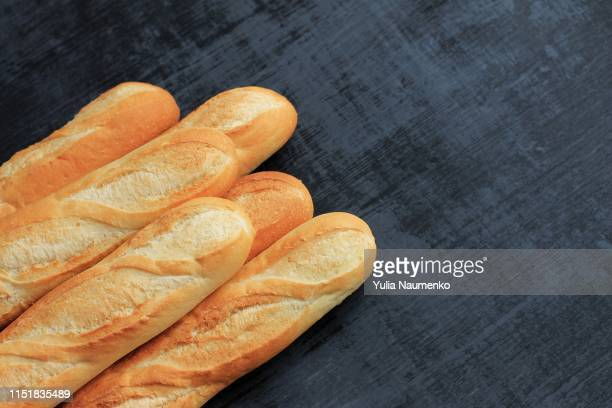 french baguettes on black wooden background. opy space. - baguette stock pictures, royalty-free photos & images