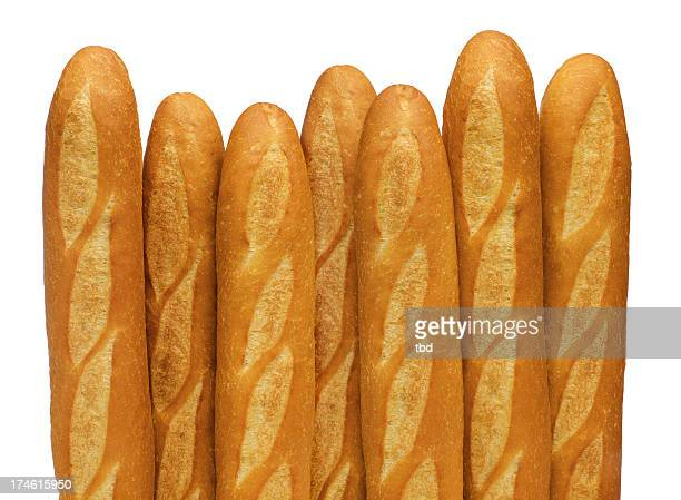 french baguettes stand vertically against a white backdrop - baguette stock pictures, royalty-free photos & images