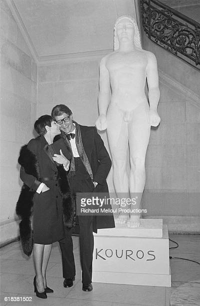 French ballerina and actress Zizi Jeanmaire whispers to fashion designer Yves Saint Laurent at the Opera-Comique during the launch of his latest...