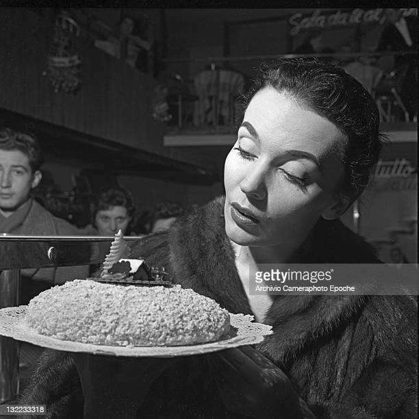 French ballet dancer Ludmilla Tcherina portrayed with a Christmas cake in a pastry shop in Milan