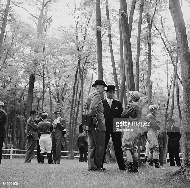 French banker and Baron Guy de Rothschild holding an umbrella chatting with his horse trainer and a jockey before the Prix de Diane horse race...
