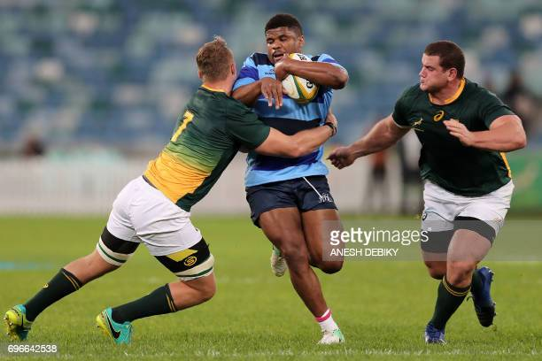 French Barbarians' Jonathan Danty is tackled by South Africa's Ruan Ackerman and Wilco Louw during the rugby union test match between French...