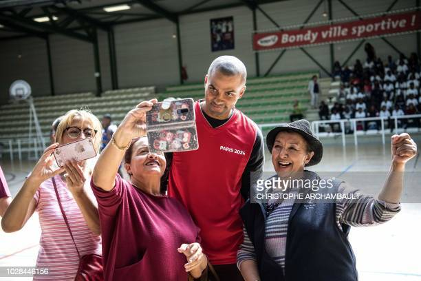 French basketball player and member of the Paris2024 olympic delegation Tony Parker poses with fans during a visit by the delegation to a secondary...