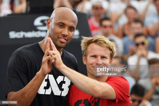 French basketball player Karim Souchu and French skipper Francois Gabart make the 'Eiffel Tower' sign with their fingers symbol of the 2024 Olympic...