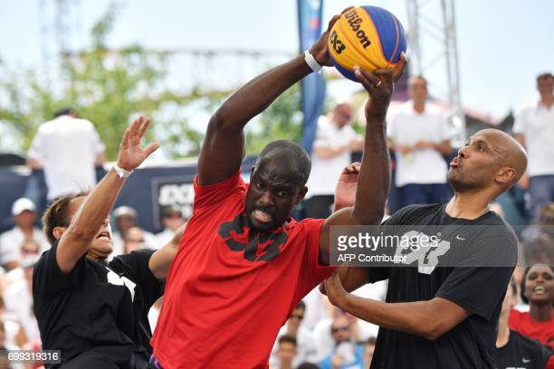 French basketball player Karim Souchu and French skipper Thomas Coville vie with French taekwondo former vice olympic champion Pascal Gentil during a...