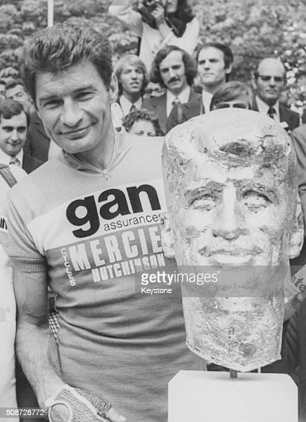 French bicycle racer Raymond Poulidor pictured at the end of the Tour de France race on the Champs Elysees with a large bust in his likeness designed...