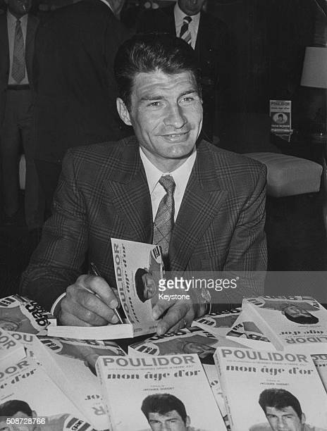 French bicycle racer Raymond Poulidor pictured signing copies of his book 'Mon Age D'Or' at a reception in Paris circa 1972