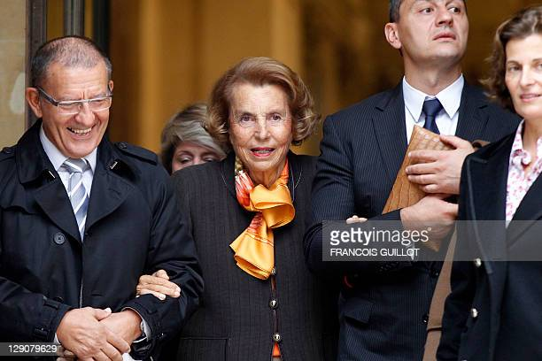 French Billionaire L'Oreal heiress Liliane Bettencourt is attended as she leaves the Institut de France in Paris after attending the official entry...