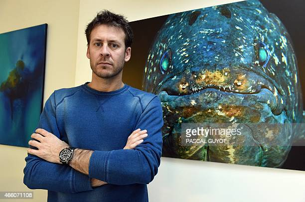 ZAKA French biologist Laurent Ballesta poses on February 16 2015 in Carnon southern France in front of one of his picture of an African Coelacanth a...