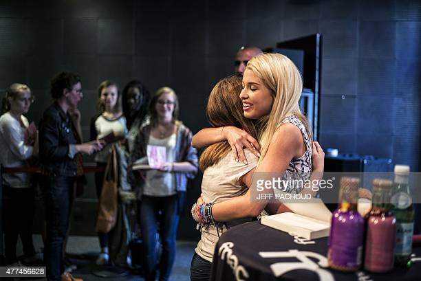 French blogger Marie Lopez aka EnjoyPhoenix gives a hug to a fan during a signing of her first book 'Enjoy Marie' on June 17 2015 in a cultural store...