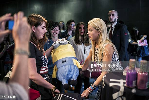 French blogger Marie Lopez aka EnjoyPhoenix receives a soft toy as a gift during a signing of her first book 'Enjoy Marie' on June 17 2015 in a...