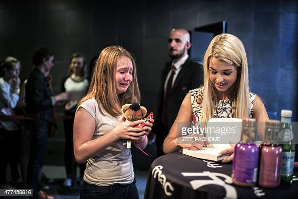 French blogger Marie Lopez aka EnjoyPhoenix stands by a crying fan who offers her a soft toy during a signing of her first book 'Enjoy Marie' on June...