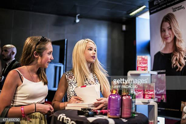 French blogger Marie Lopez aka EnjoyPhoenix stands by a fan during a signing of her first book 'Enjoy Marie' on June 17 2015 in a cultural store in...