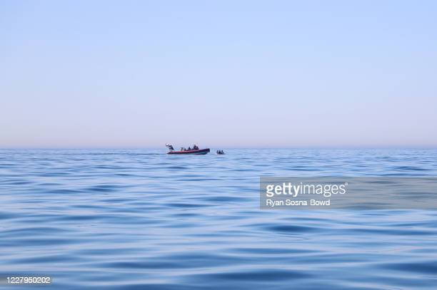 French border police bo2at escorts a dinghy carrying migrants attempting to cross the English Channel on August 7, 2020 off the coast of France....