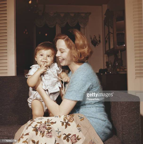 French born actress Leslie Caron holds her son Christopher Hall at her flat in London in March 1958.