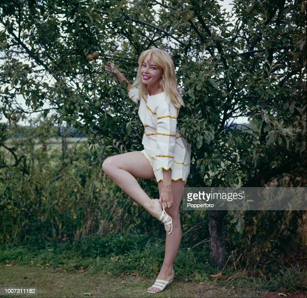 French born American actress Leslie Caron pictured standing next to a fruit tree in England in 1961.