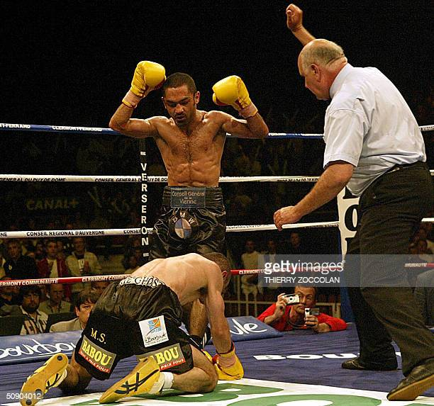 French boxer Mahyar Monshipour raises his arms in victory as compatriot Salim Medjkoune is knocked down 27 May 2004 in ClermontFerrand during their...