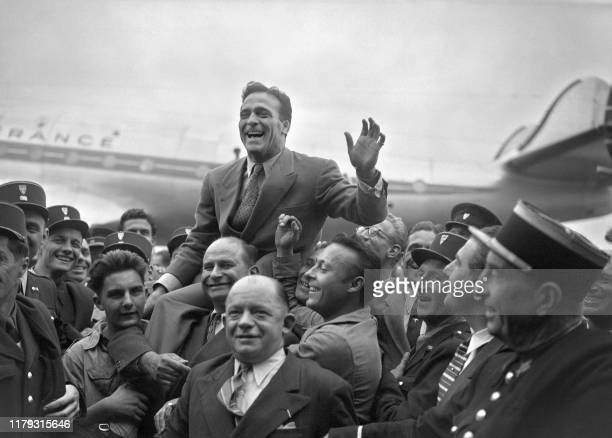 French boxer Marcel Cerdan is welcomed by a cheering crowd, 01 October 1948 upon his arrival at Orly airport, as he returns from the United States,...