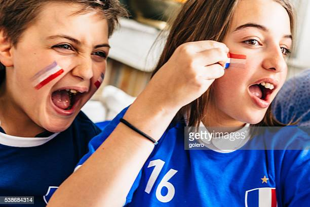 french boy and girl soccer fans with face painting - girl sitting on boys face stock photos and pictures