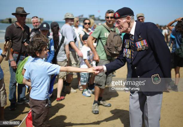 French boy Efflam Chavanes aged 8 from Caen thanks DDay veteran Joseph Kellsey as he walks on Sword Beach during the 70th anniversary of the DDay...