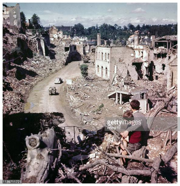 French boys sit and observe some Allied vehicles passing through the French World war two damaged City of Saint-Lô, 1944.