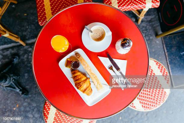 french breakfast with fresh croissant, baguette bread, coffee and orange juice served in cafe, high angle view - france stock-fotos und bilder