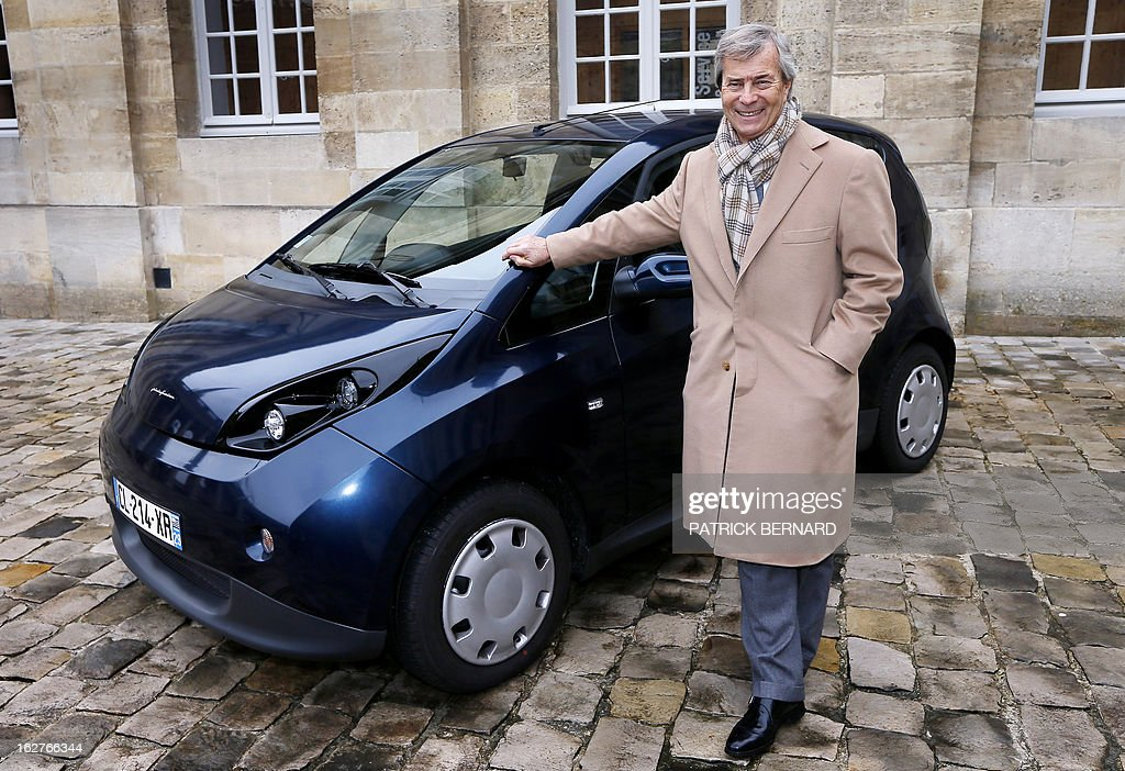 French businessman Vincent Bollore poses on February 26, 2013 with his electric Bluecar at the Bordeaux Town Hall as part of the car's presentation to the city's Mayor Alain Juppe.