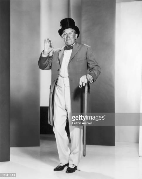 French cabaret singer and actor Maurice Chevalier poses with a top hat and cane and makes the 'OK' hand sign in a promotional portrait for director...