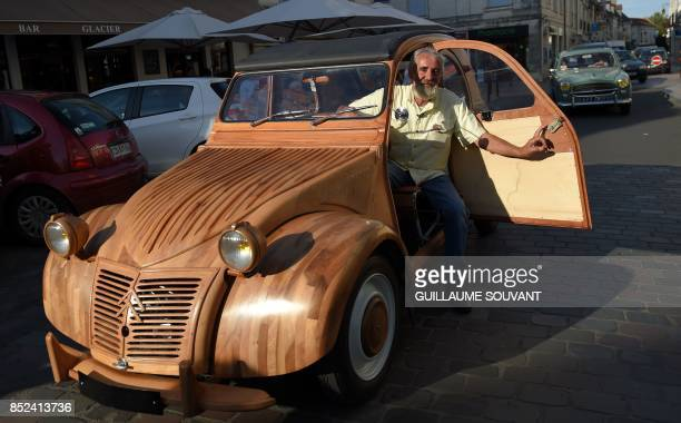 French cabinetmaker Michel Robillard poses in his wooden 2CV Citroen car in the streets of Loches Central France on September 23 2017 A retired...