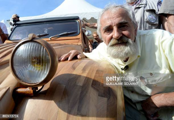 French cabinetmaker Michel Robillard poses next to his wooden 2CV Citroen car in the streets of Loches Central France on September 23 2017 A retired...