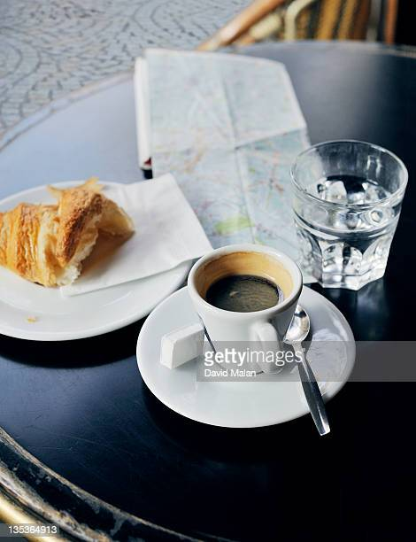 French cafe table with coffee, croissant and a map