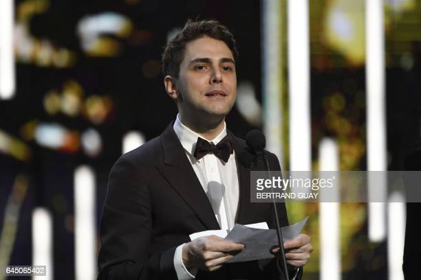 French Canadian actor and film director Xavier Dolan speaks on stage as he takes the Best Actor award won by French actor Gaspard Ulliel for 'Juste...