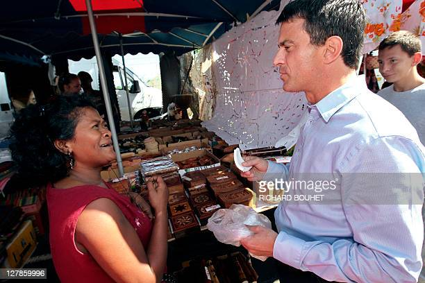 French candidate for the 2011 Socialist party primary vote for France's 2012 presidential election Manuel Valls tastes a fruit offered by a vendor as...