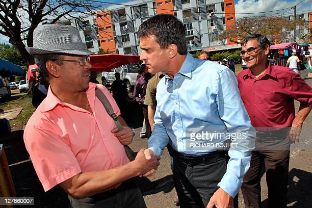 French candidate for the 2011 Socialist party primary vote for France's 2012 presidential election Manuel Valls shakes hand to a man as he visits the...