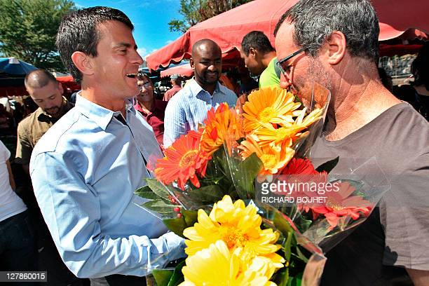 French candidate for the 2011 Socialist party primary vote for France's 2012 presidential election Manuel Valls speaks with a man as he visits the...