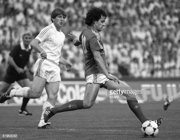 French captain and midfielder Michel Platini eyes the ball as Yugoslav Safet Susic looks on during the European Nations soccer championship match...