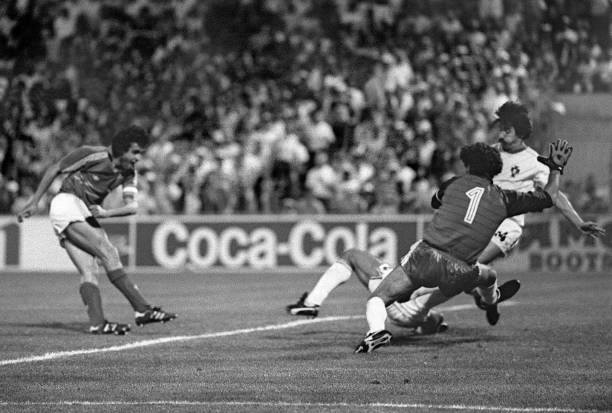 French captain and midfielder Michel Platini scores the winning goal in extra time as Portuguese goalkeeper Bento and defender Frasco dive in vain...