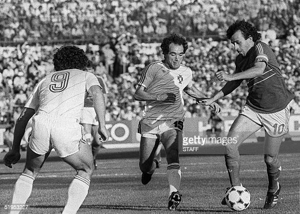 French captain and midfielder Michel Platini tries to dribble by Portuguese Jaime Pacheco as Joao Pinto looks on during the European Nations soccer...