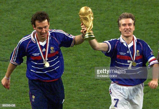 French captain Didier Deschamps and Laurent Blanc hold the FIFA trophy after the 1998 Soccer World Cup final between Brazil and France at Stade de...