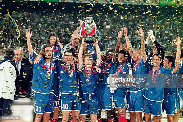 French captain Didier Deschamps lifts the trophy amidst his teammates after France wins the 2000 UEFA European Championship final, France vs Italy .
