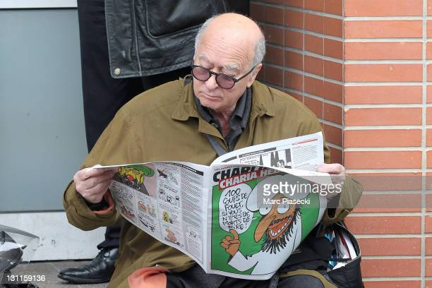 French cartoonist Georges Wolinski reads a copy of 'Charlie Hebdo' as he sits in front of the French satirical magazine offices following a petrol...