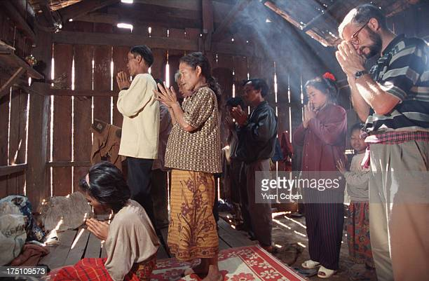 French Catholic missionary Gerald Vogin leads a group of Phnong villagers in prayer in a wooden hut A small group of Phnong montagnards usually...