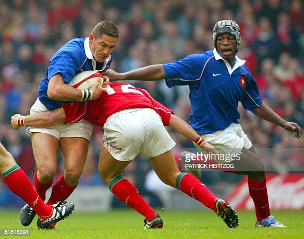 French center Tony Marsh is tackled by Welsh center Andy Marinos as French flanker Serge Betsen looks on during the Wales/France 6 Nations rugby game...
