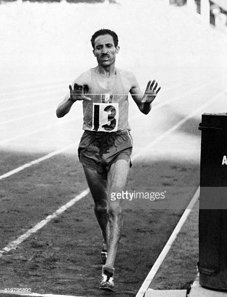 French champion Alain Mimoun crosses victoriously the finish line of the Olympics marathon event on November 22 1956 at the Olympic stadium in...