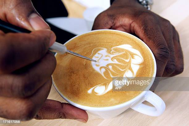 French champion of latte art Rudy Dupuy prepares a creation during the exhibition 'World of coffee' on June 27 in Nice southeastern France AFP PHOTO...